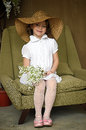 Little girl with a smile in a wide brimmed straw hat in a bouquet of white lilies of the valley in the hands art studio portrait Royalty Free Stock Photo