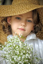 Little girl with a smile in a wide brimmed straw hat in a bouquet of white lilies of the valley in the hands art studio portrait Stock Images
