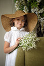 Little girl with a smile in a wide brimmed straw hat in a bouquet of white lilies of the valley in the hands art studio portrait Stock Photo