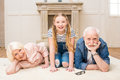 Little girl with smiling grandpa and grandma resting together at home Royalty Free Stock Photo