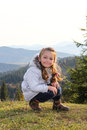 Little girl smiling while sitting down on top of the mountain Royalty Free Stock Images