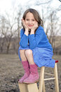 Little girl smiling and sitting on a stepstool holding her face in her hands red white vintage wearing pink suede boots Royalty Free Stock Photos