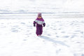 Little girl on the snow walking in Stock Photo