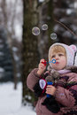 Little girl with soap bubles in winter Royalty Free Stock Photo