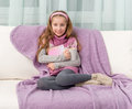 Little girl on sofa with the book Royalty Free Stock Photo
