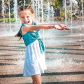 Little girl in splashes a fountain cute having fun Stock Images