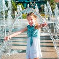 Little girl in splashes a fountain cute having fun Royalty Free Stock Image