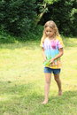 Little girl splashing water barefoot walking on a meadow and from a bottle Royalty Free Stock Images