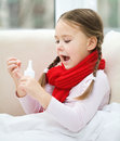 Little girl spraying her nose with nasal spray while sitting on sofa Royalty Free Stock Photography