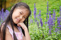 Little girl squat in flowers asian the park Royalty Free Stock Photos
