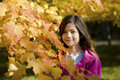 Little girl standing by autumn leaves Stock Photo