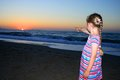 Little girl standing on the beach and looking at sunset Royalty Free Stock Photos