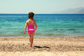 Little girl standing on beach in swimsuit and going to swim the sea rear view summer holidays Royalty Free Stock Photo