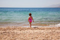 Little girl standing on beach in swimsuit rear view the a summer holidays Stock Photo