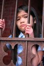 Little girl standing behind iron bars with sad expression wither looking in or out of gate or prison Stock Photo