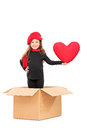 Little girl standing in box with a red heart and holding isolated on white background Royalty Free Stock Image