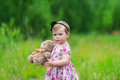 Little girl standing in grass holding large teddy bear. Royalty Free Stock Photo