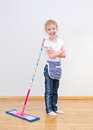 Little girl standing near mop at home. Royalty Free Stock Photo