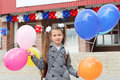 Little girl standing outdoor with color balloons Royalty Free Stock Image