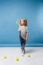 Little girl standing with tennis raquet and balls on blue Royalty Free Stock Photo
