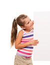 Little girl is standing on white background and holding white ca i can hold this piece of cardboard where could be your Stock Image