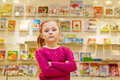 Little girl stands with arms folded on chest in book department of store against showcase books Stock Photo