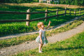 Little girl stands on the country raod and point on somtheing