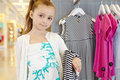 Little girl stands holding gown over her arm striped in clothing store Royalty Free Stock Photo