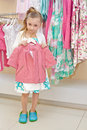 Little girl stands holding hanger with jacket pink Stock Image