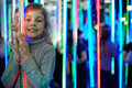 Little girl stands in mirror labyrinth illuminated with color lights Stock Images