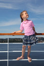 Little girl stands at railing on deck of ship Stock Images