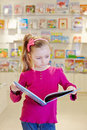 Little girl stands reading open book in department at store Royalty Free Stock Photos