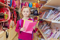 Little girl stands in school department of store with backpack on shoulders holding several notebooks Royalty Free Stock Images