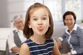 Little girl sticking tongue cute making funny face granny and mother looking from background Royalty Free Stock Image