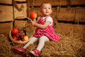 Little girl on straw with a basket of fruits Stock Photo