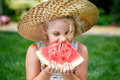 Little girl in straw hat with big slice of watermelon sitting on green grass in summer park.