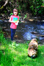 Little girl by stream with doggie a exploring and playing a in the woods a shallow depth of field Stock Photography