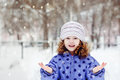 Little girl stretched out her hand in which the falling snowflakes winter portrait Stock Photo