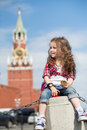 The little girl in stylish dress near the kremlin sitting on concrete with a compass hand Royalty Free Stock Photography