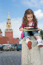 Little girl in stylish dress sitting on concrete the cute near the kremlin and looking the map with magnifier Royalty Free Stock Image