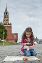 The little girl in stylish dress sitting near the kremlin on sett and looking on map with magnifier Stock Photos