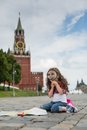 The little girl in stylish dress sitting near the kremlin on sett with map and looking through a magnifying glass Stock Image