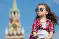 Little girl in stylish dress and sunglasses sitting near the kremlin Stock Photos