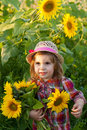 Little girl in a summer hat among sunflowers Stock Images
