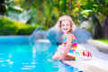 Little girl in a swimming pool adorable with curly hair wearing colorful suit playing with water splashes at beautiful tropical Stock Images