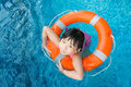 Little girl in swimming pool asian with orange water ring Stock Image
