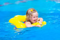 Little girl in swimming pool cute funny toddler a colorful suit and sun glasses relaxing on an inflatable toy ring floating a Royalty Free Stock Photography