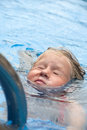 Little girl in swimming pool funny face of on blue water background Stock Photography