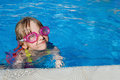 Little girl swimming in pool with goggles Stock Images
