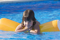Little girl in a swimming pool on an inflatable mattress Stock Photography